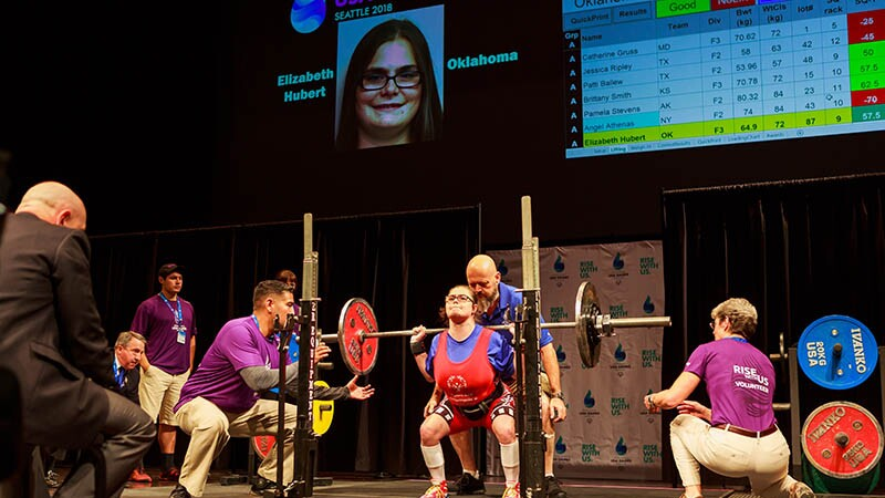 Liz Huber, Oklahoma Special Olympics athlete on stage squatting at the USA 2018 Games in Seattle. A male spotter is standing behind her and and one either side of the weights. An official is in the foreground watching her performance.