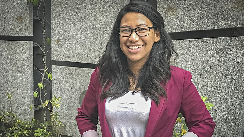 Aloysia, a young woman wearing glasses , a purple blazer, gray shirt, and big smile standing in front of a garden wall.
