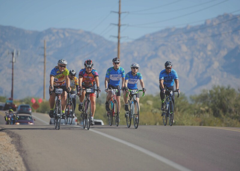 A group of 6 cyclists riding down a road in a rural area.