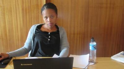 Swaziland volunteer sitting behind a desk at a computer.