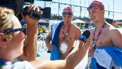 Two swimmers—post race—being interviewed by the press by the swimming pool.