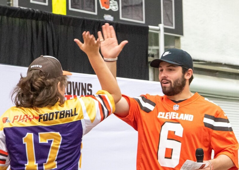 Baker Mayfield giving a high five to a special olympics athlete