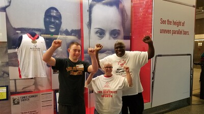 Ricardo Thornton and wife, Donna, at the Smithsonian in Washington, D.C., with Special Olympics Virginia athlete Gavin Brodie. All three are standing in front of Ricardo's display with their hands up in celebration.