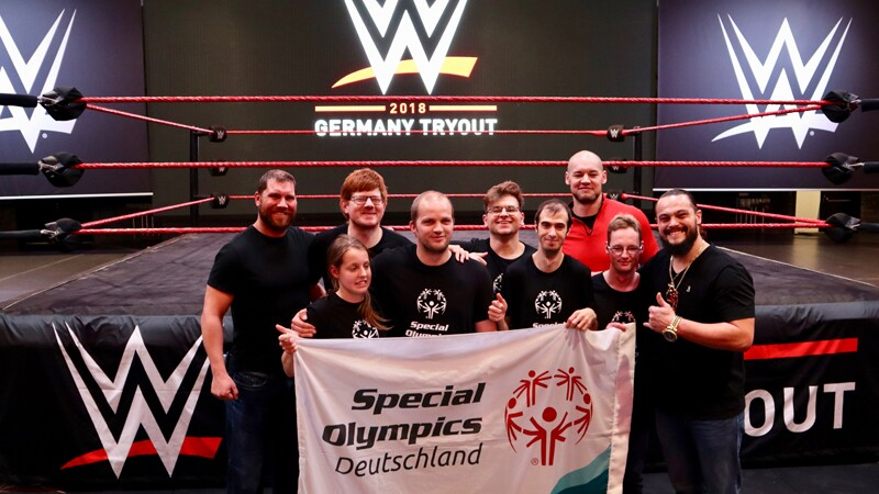 WWE NXT Tryout participants and SO Deutschland athletes after unified workout standing in front of the ring holding a SO Deutschland banner.