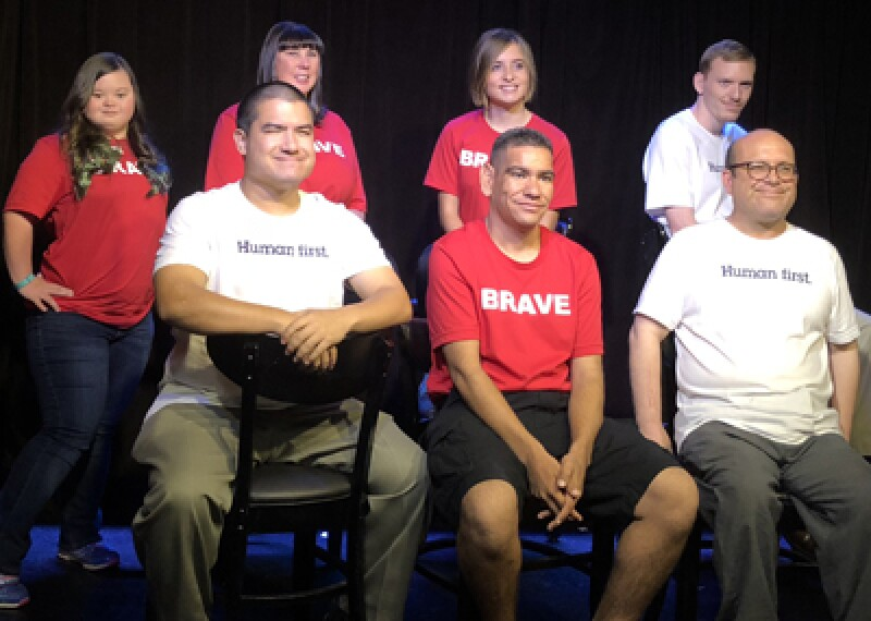 Special Olympics athletes in a group in front of a black backdrop. Athletes have on prinkshop t-shirts. Red shirts read, Brave; white shirts read, Human First.