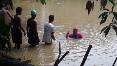 Arpita wading in the water instructing athletes on how to swim.