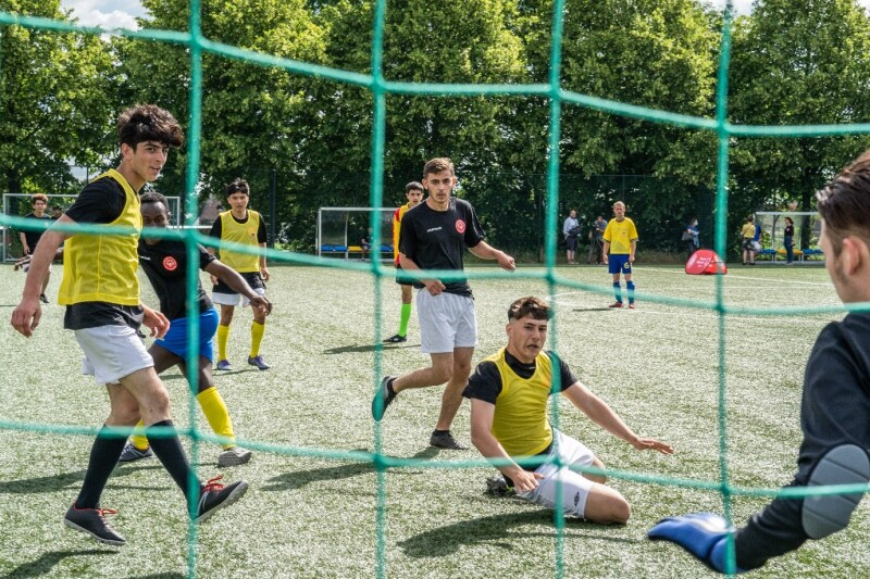 A group of young men in t-shirts, shorts and bibs in action facing the goal on a football pitch.