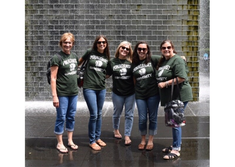 Five teachers wear green Ponaganset shirts and stand in front of fountain.