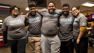 Five young adults wearing Spread the Word Inclusion t-shirts.